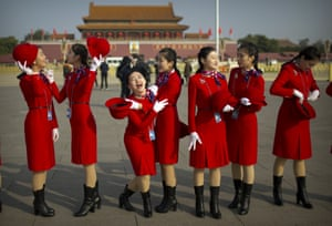 Hospitality staff members laugh as they stand on Tiananmen Square