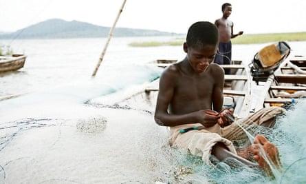 young boy repairing a fishing net