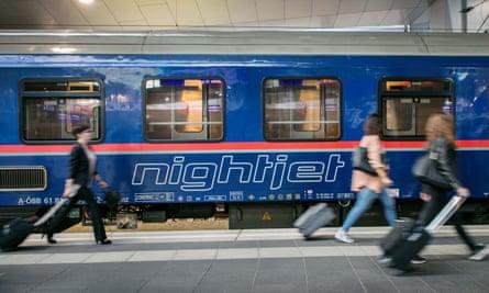Nightjet sleeper train in a station, in Austria, as travellers get ready to board it.