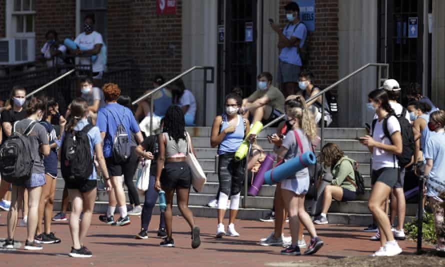 University of North Carolina students wait outside Woolen Gym on the Chapel Hill campus as they wait to enter for a fitness class on Monday,