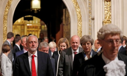 Britain's Prime Minister Theresa May (second right)  and Labour party Leader Jeremy Corbyn (left) walk through the Peer's Lobby during the State Opening of Parliament in the Houses of Parliament in London on June 21, 2017.