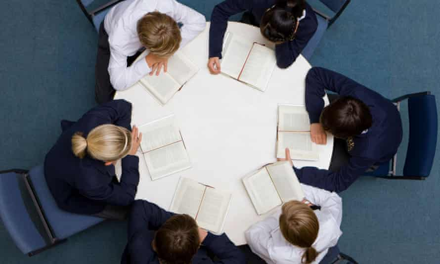 Students reading at round table in school library