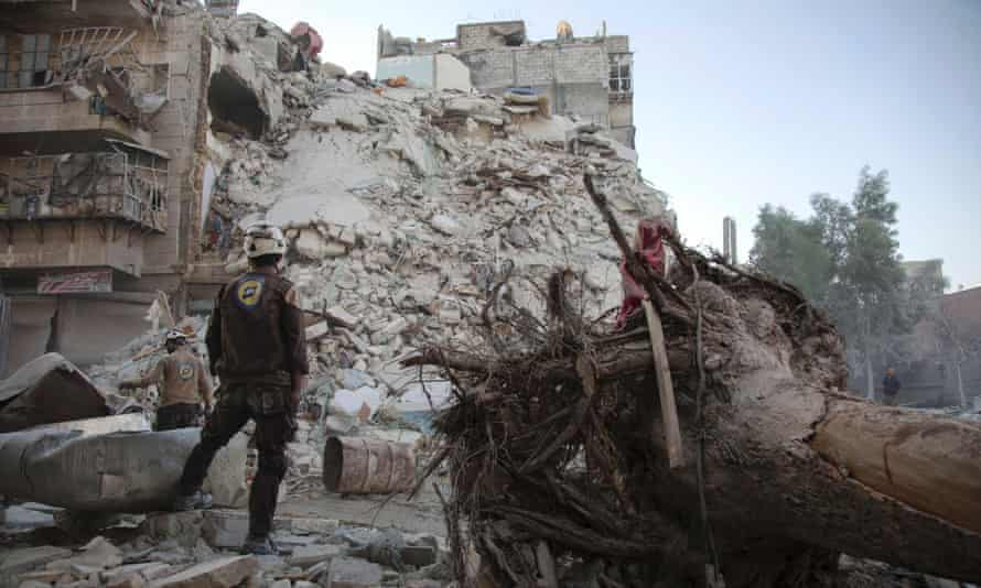 A member of the White Helmets stands amid the rubble of a destroyed building after airstrikes in Aleppo in October.
