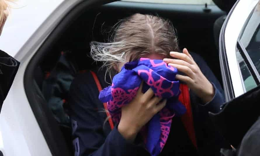 A British woman, accused of lying about being gang raped, covers her face as she arrives at the Famagusta courthouse in Paralimni, Cyprus.