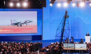 The video screen shows the Kinzhal air missile system as Russia's President Vladimir Putin (R) delivers his annual address