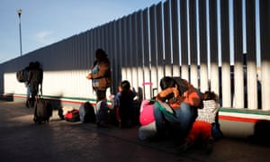 A migrant man sits with his children at the border in Tijuana, Mexico, as they wait to hear if their number is called to apply for asylum in the US, on 25 January.