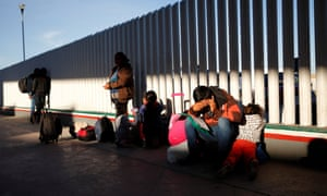 A migrant sits with his children as they wait to hear if their number is called to apply for asylum in the US, at the border, in Tijuana, Mexico, on January 2019.