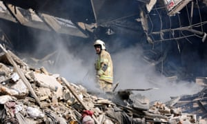 A rescue worker stands in rubble from the Plasco building.