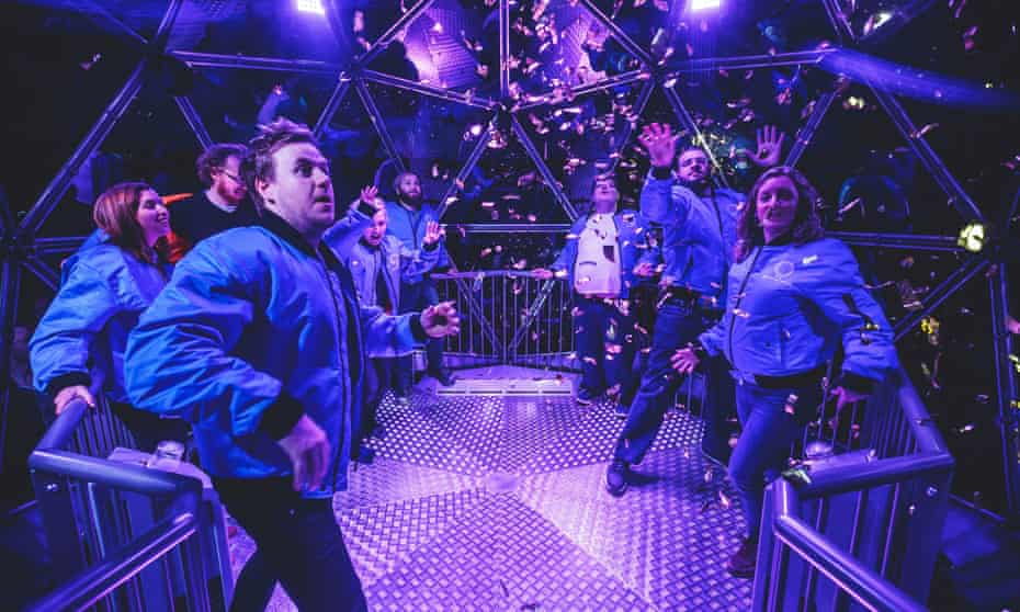 Contestants in a glass dome as part of the Crystal Maze game finale, a new interactive game in London, where they have to grab at foil tickets.