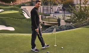 Mark Wahlberg with a golf club, standing by a golfing hole, with the course and tennis courts in the background
