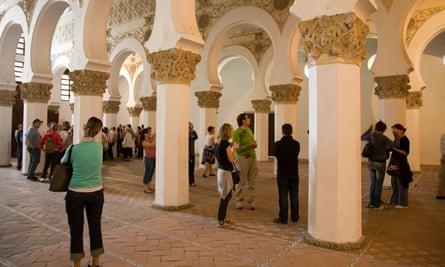 Visitors view horseshoe arches and wall carvings at Santa María la Blanca.