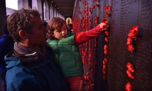Angus White watches as his daughter Scarlett puts a poppy beside her great grandfather's name, after the dawn service at the Australian War Memorial in Canberra.