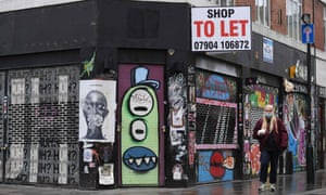 A woman wearing a face mask walking past a vacant shop in east London