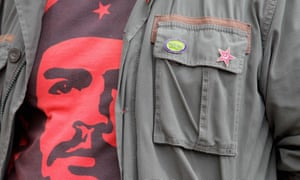 Demonstrator wears a Che Guevara T-shirt under a khaki jacket with a hammer and sickle badge