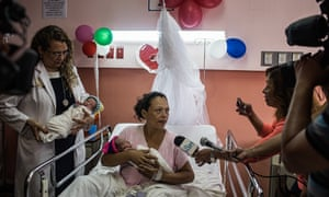Brenda Molina sits in a hospital bed holding one her twins with reporters and Doctor María Isabel Rodríguez holding the second baby
