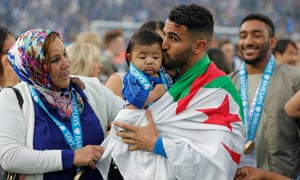 Leicester City's Algerian midfielder Riyad Mahrez kisses his daughter Inaya as the players celebrate the League title.