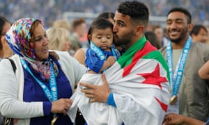 Riyad Mahrez kisses his baby daughter Inaya as the players celebrate the League title