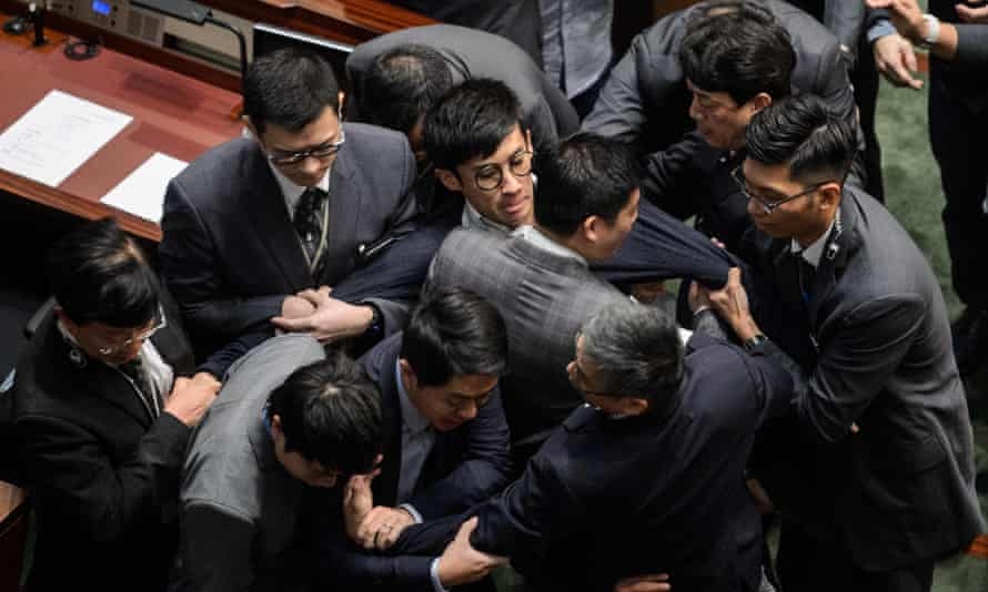 Leung (centre, wearing glasses) is restrained by security after attempting to read out his oath of office.