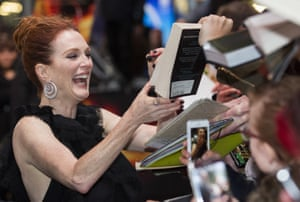 Julianne Moore signs a copy of the Hunger Games book