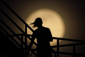 A girl watches the moon rise from an observation tower in New Albany, Indiana, US.