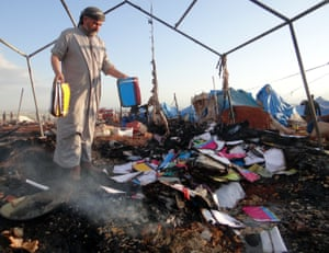 A man inspects the damage at Syria refugee camp