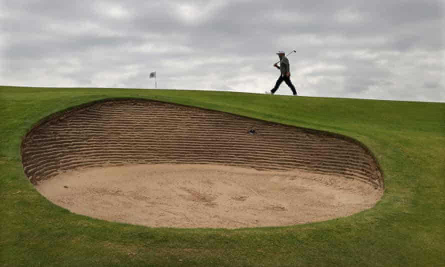 Louis Oosthuizen walks along the 10th green past a monster bunker at Royal St George's.