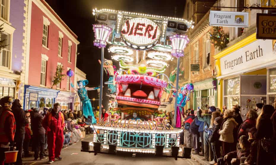 Rolling on: the carnival arrives in Glastonbury, lights reflected in the crystal shops.