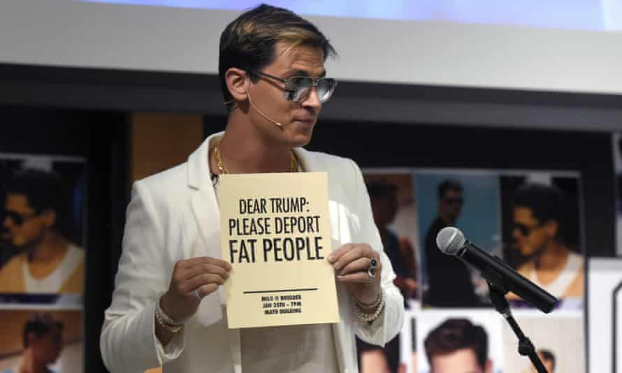Milo Yiannopoulos holds a sign as he speaks at the University of Colorado campus in Boulder