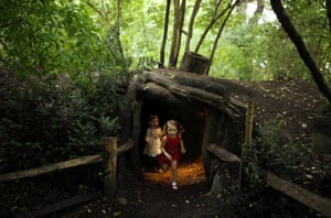London, UK Children play inside an area designed to look like a badger set at Kew Gardens. The summer festival includes a newly opened 16 hectare area of the woodland and wildflower meadow