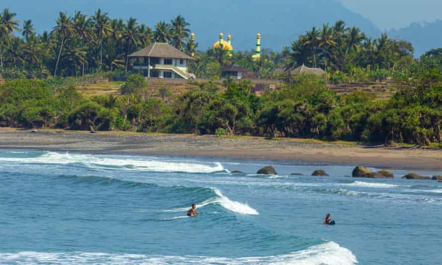 Balinese children surf a wave at Medewi beach, Indonesia