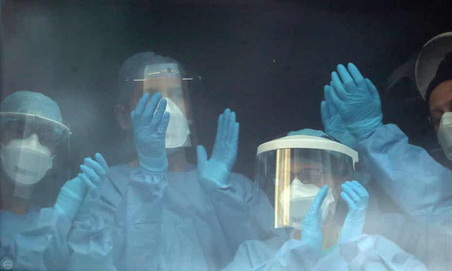 Nursing staff applaud at a window inside the Queen Elizabeth University Hospital in Glasgow.