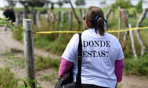 """A woman from Solecito Collective, a support group for parents of missing children, wears a shirt that reads """"Where are you?"""" as she stands near the site of a mass grave in Veracruz, Mexico."""