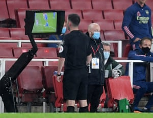 Referee Chris Kavanagh looks at the VAR screen before sending off Arsenal's Eddie Nketiah.