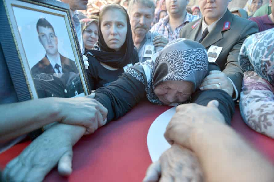 Fatma Sarpkaya mourns over the coffin of her son, Ziya Sarpkaya, who was shot by a masked separatist.