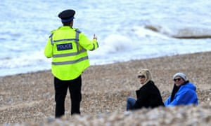 A police officer speaks to people on the beach in Brighton.