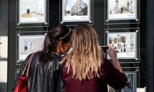 Women studying houses for sale in an estate agent's window.