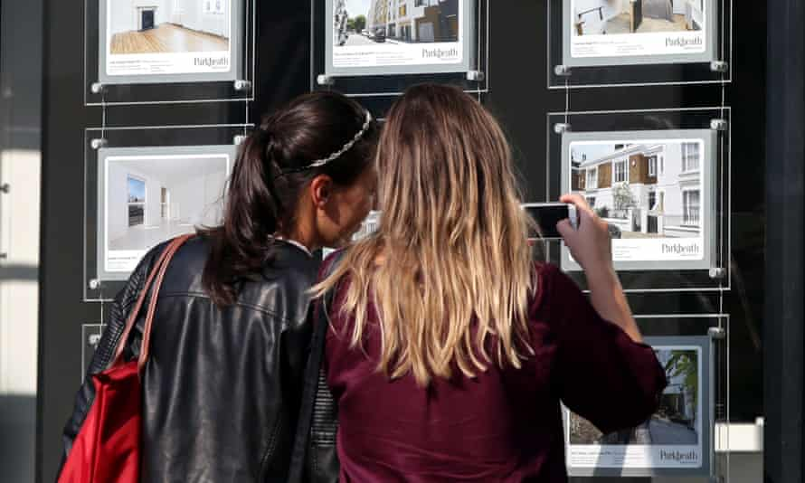 Two young women study an estate agent's window in London. Record numbers of young Britons cannot afford to move out of their parents' home.