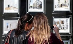 Two women look in the window of an estate agency