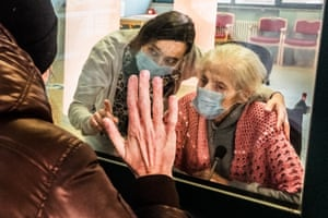 Milan, Italy: Relatives meet through protective glass that allows guests to meet relatives at the Casa Madonna della Fiducia care home in Calolziocorte