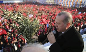 Recep Tayyip Erdoğan holds olive branches as he addresses party members