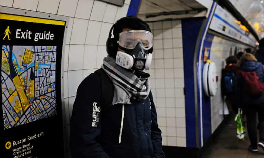 A person wearing a full-face mask in King's Cross underground station