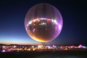 An inflatable sphere covered in reflective material hangs over the dusty playa of Burning Man, reflecting back the neon and LED lights scattered around the area