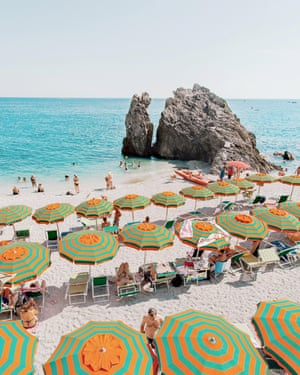 """The beach at Monterosso al Mare, Italy, busy with people and with colourful (green and orange-coloured) beach umbrellas.  """"It's not a destination for peace and quiet, but this seaside town has managed to retain its historical charm with its beach umbrellas, terraced houses, steep stairways and dramatic cliffs."""""""