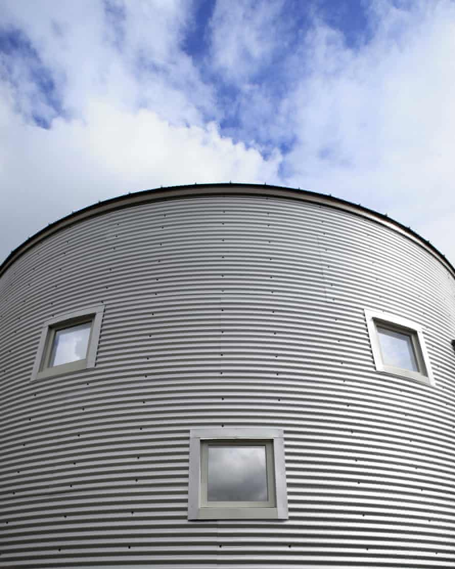 Windows on a corrugated metal building that look like a face