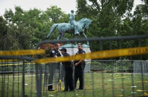 Police stand watch near the statue of Confederate General Robert E. Lee in the center of Emancipation Park