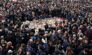 People hold a minute of silence around a makeshift memorial at Place de la Bourse.