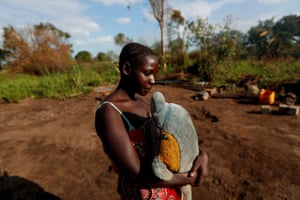 Maria Jofresse, 25, holds a stuffed toy on the spot where her house stood before its destruction by Cyclone Idai. Jofresse lost her two children to the storm.