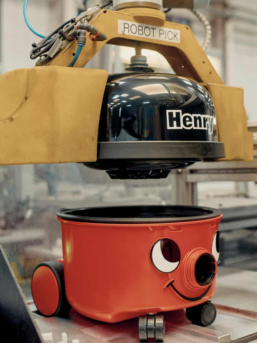 A robot attaching a lid to a Henry vacuum cleaner on the assembly line.