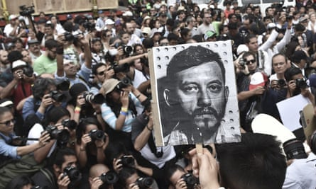 Mexican photojournalists hold pictures of their murdered colleague Ruben Espinoza during a demostration held at the Angel of Independence square in Mexico City.