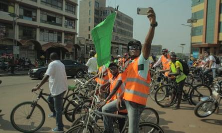 A Critical Mass cyclist takes a selfie as the group waits to cross Kampala Road.